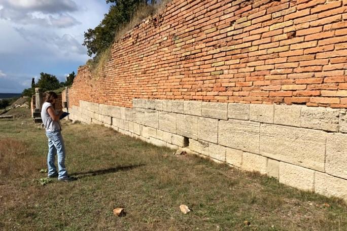 L'architecte M. Huille esquisse sur sa tablette le relevé architectural de la courtine avec une élévation en briques.